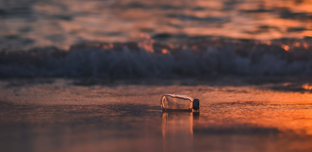 Discarded bottle on the sea shore