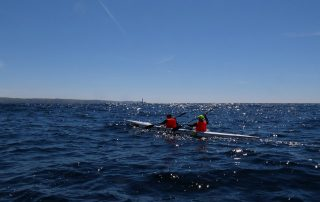 Paddlers in sight of land and the Longships Lighthouse on the Celtic Crossing